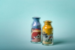 Handmade souvenir. Small bottle with drawings made with colored sand, typical of the northeast region of Brazil on an infinite greenish background.