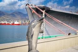 Handmade stone dolphin statue near the sea.