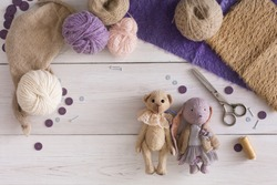 Handmade toy making, artisan workplace top view. Bear and rabbit with materials for creating vintage plaything, home workshop, copy space for text