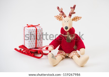 Handmade toy vintage Christmas deer sitting on light background with gift box