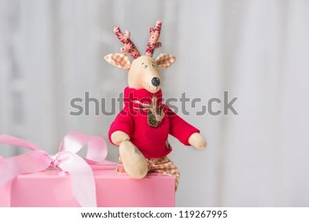 Handmade toy vintage Christmas deer sitting on the pink gift box