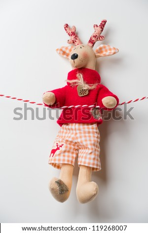 Handmade vintage Christmas deer hanging on a ribbon on white background