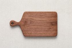 Handmade walnut chopping board on burlap. Culinary chopping board background.
