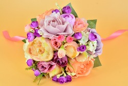 Handmade wedding bouquet with artificial flowers isolated on orange background / Silk flowers