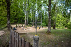 handmade welded metal cross on old country cemetery gate pylon. Burial places in background. Traditional country graveyard in Latvia