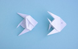 Handmade white trendy geometric polygonal paper origami fish on blue background.Step 3.