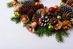 Handmade wooden Christmas jingle bell, fir branches and pine cones. Christmas decoration with ornaments and dried orange slices. Christmas greeting background. Copy space.