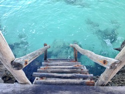 Handmade wooden ladder leading down to clear blue Caribbean water from a wooden dock in Cozumel, Mexico.