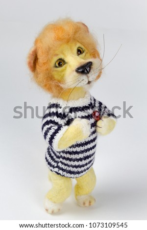handmade wool toy lion with red heart and striped wool jumper standing #1073109545