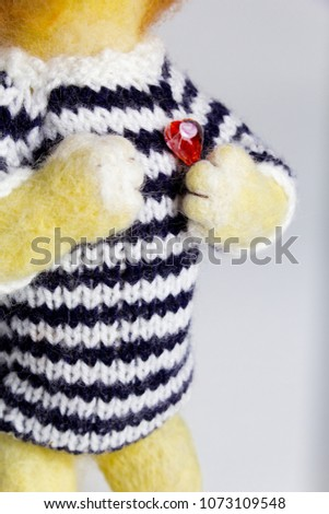 handmade wool toy lion with red heart and striped wool jumper standing #1073109548