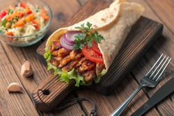 Handmade wrap doner kebab is lying on the cutting board. Burrito. Shawarma with chicken meat, onions, salad lies on a dark old wooden table.