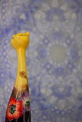 Handmade yellow cat porcelain with a pattern sculpture of flowers. It is a souvenir used to present gifts, and the background is a fabric cloth with a blurred flower pattern.