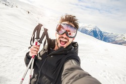Handome skier in the snow taking a selfie on a mountain. Portrait of a funny and crazy guy at vacation in winter.