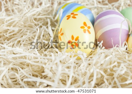 Handpainted Easter eggs situated in upper right portion of frame, in a simulated straw nest of shredded paper.