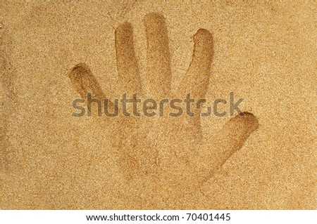 handprint in the sand of a beach
