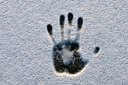 Handprint in the snow. The effect of human heat on snow. Hand print in snow
