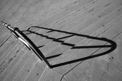 Handrail and shadow on flight of steep stairs might induce vertigo in some (monochrome image).