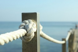 Handrail with ropes against sea, close up