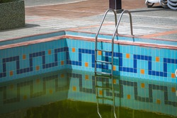 Handrails for dirty water pool. Swimming pool with ladder in a tropical resort. Steel railings, swimming, summer, travel. Entrance to the pool with railings.