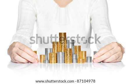 Hands adding a stack of coins to savings