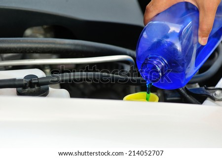 hands adding auto glass cleaner for car