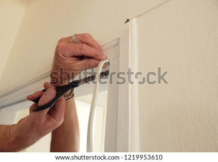 hands affixing adhesive rubber draft proofing to a door frame.