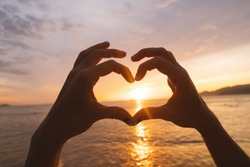 Hands and fingers in heart shape framing setting sun at sunrise over ocean