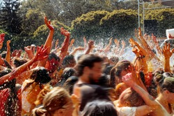hands and happy people crowd partying under rain at holi fest, festival of colors in summer, amazing moment