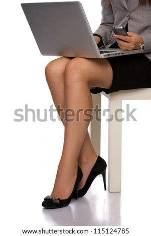 Hands and legs of an elegant woman with a laptop and a phone