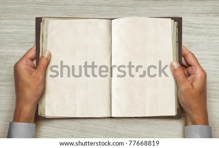 hands and opened vintage book over table