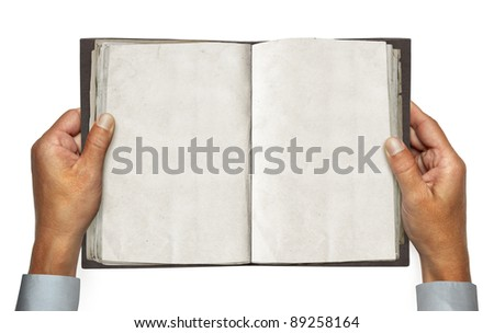 hands and opened vintage book over white background with path