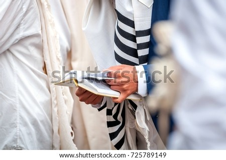 Hands and prayer book close-up. Orthodox hassidic Jews pray in a holiday robe and tallith