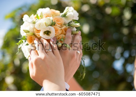 Hands and rings of the bride and groom on wedding bouquet #605087471
