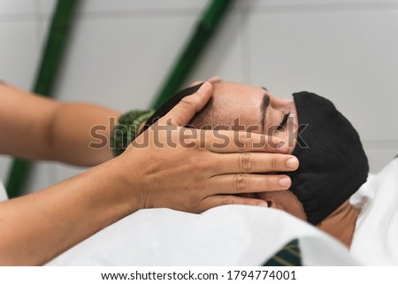Hands applying reiki on the head of a young woman during a therapy, to unlock the crown chakra during coronavirus crisis. Health care and alternative medicine concept Stock photo ©