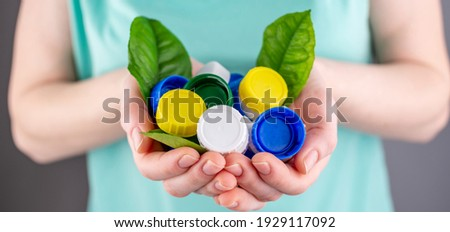 Hands are holding a handful of colorful plastic lids with green leaves. Concept of environmental pollution, eco friendly behavior, waste sorting and plastic recycling. Stockfoto ©