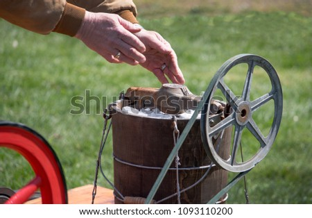 hands are seen adding ice to an old fashioned ice cream maker that is pulley and gas driven to mix up the dessert #1093110200