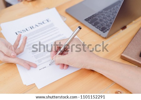 Hands are signing insurance contract.Contract agreement policy concept.