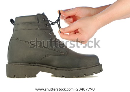 Hands are tie shoe-laces on a rough boot on a high thick sole