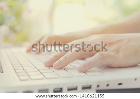 Hands are used on the laptop's keyboard. #1410621155