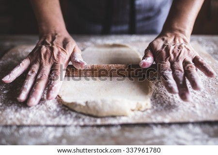 Hands baking dough with rolling pin on wooden table, depth of field