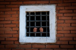 Hands behind the bars in a brick prison. Prisoner in a Far-Western style set.