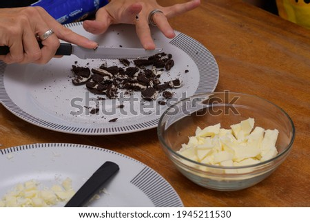 Hands breaking cookies to make easter eggs and pots with white c stock photo