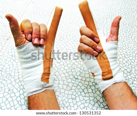 hands breaking of bones wrapped in bandages and plasters