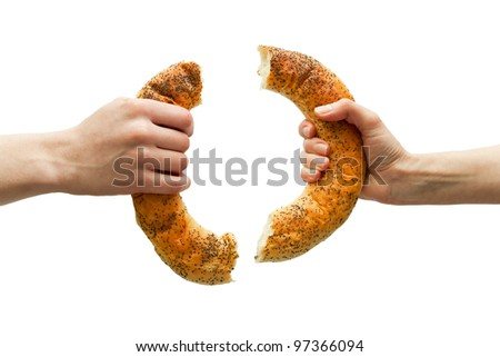 Hands breaking ring bread isolated on white. Sharing concept