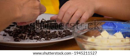 Hands breaking up cookies to make easter eggs stock photo
