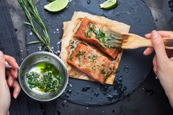 Hands brush the marinade is applied to a piece of salmon on a slate stone on a dark metallic background. View from above. Preparation for cooking fish food. Salmon steak. Woman cook.