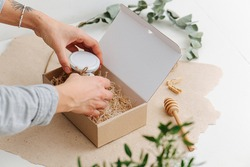 Hands carefully placing small jar with honey in a box with filling paper. Over white surface, decorated with a branch.
