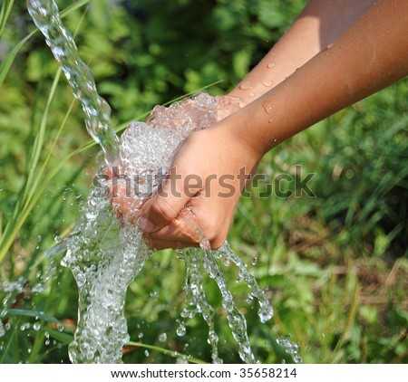 Hands catching clean falling water close up