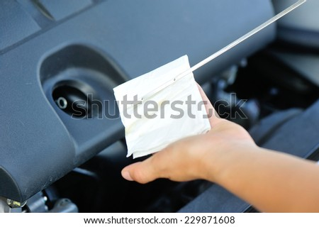 hands checking the car engine oil