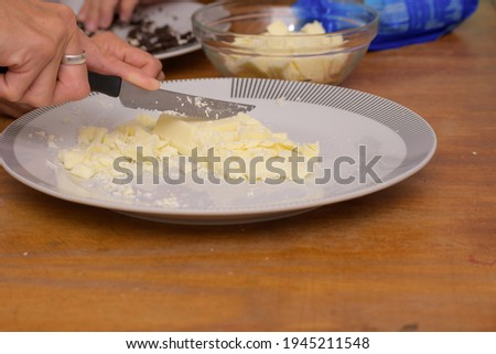 Hands chipping white chocolate to make easter eggs stock photo